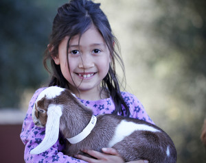 Farm kid Nicole holding one of ther favorite goats